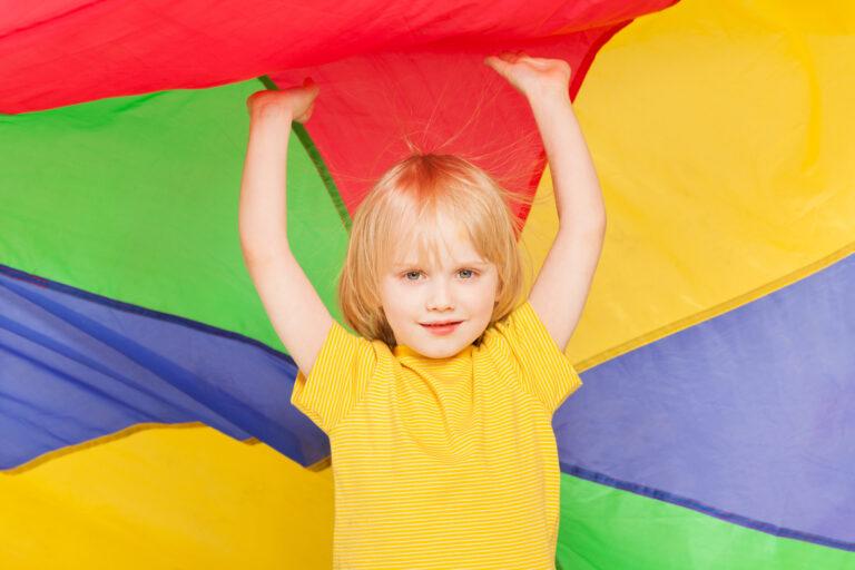 Boy hiding under canopy made of rainbow parachute