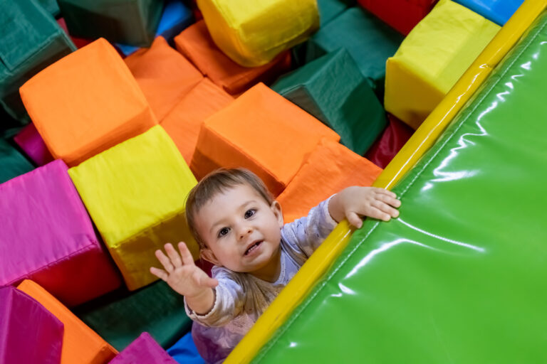 little cute toddler girl in a dress in the pool with cubes looks at the camera and pulls her hand up to climb out on the playground in the children's play center. top view