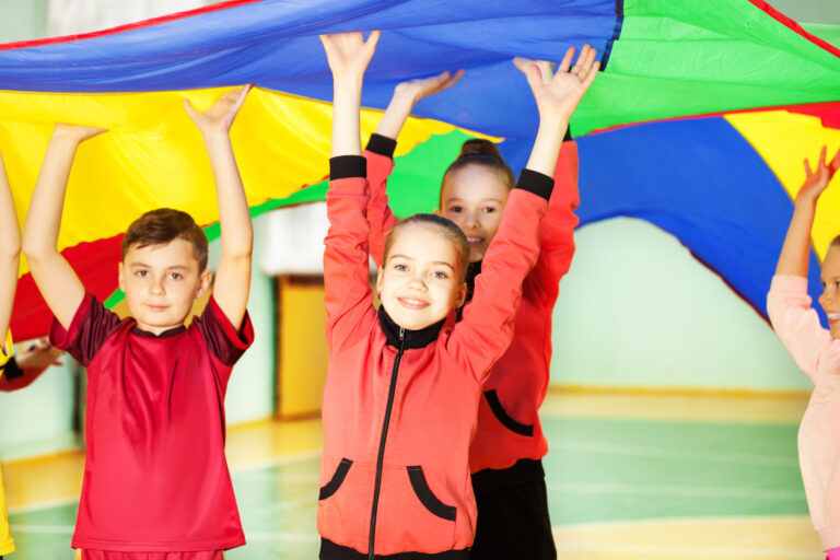 Happy friends jumping under the parachute