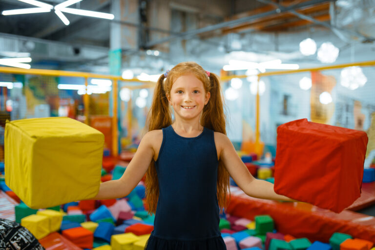 Adorable little girl playing with soft cubes, playground in entertainment center. Play area indoors, playroom